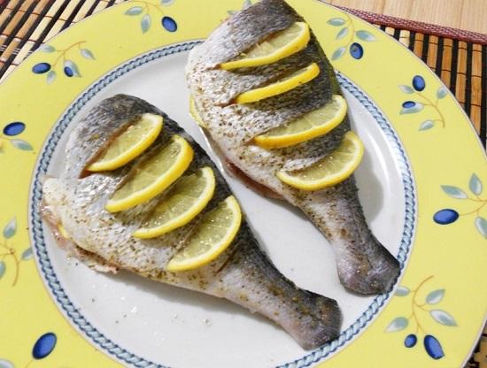в надрезы на спинке вставляем ломтики лимона