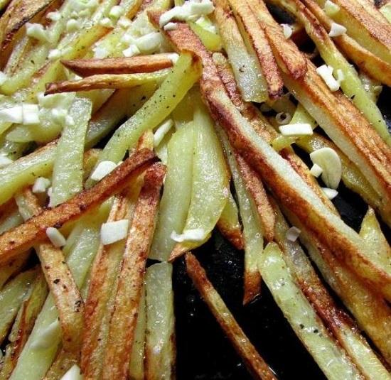 посыпаем картофель и куриные бедра измельченным чесноком