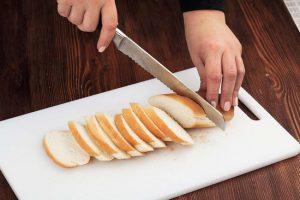 Нарежьте батон на ломтики, располагая лезвие ножа под углом