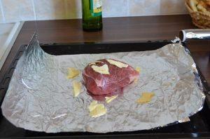 Сверху мяса положим несколько масляных кусочков