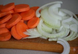 Нарежьте лук и морковь тонкими кружочками