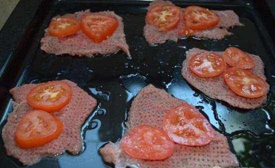 Кружочки помидоров выложите поверх отбивных