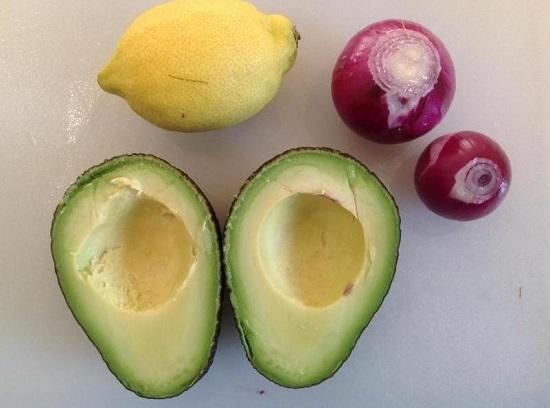 Авокадо разрезаем пополам и удаляем косточку