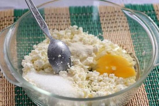 Добавьте к творогу яйцо, сахар, положите манку