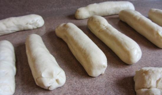 Оборачиваем сосиски тестом, формируя из них колбаски